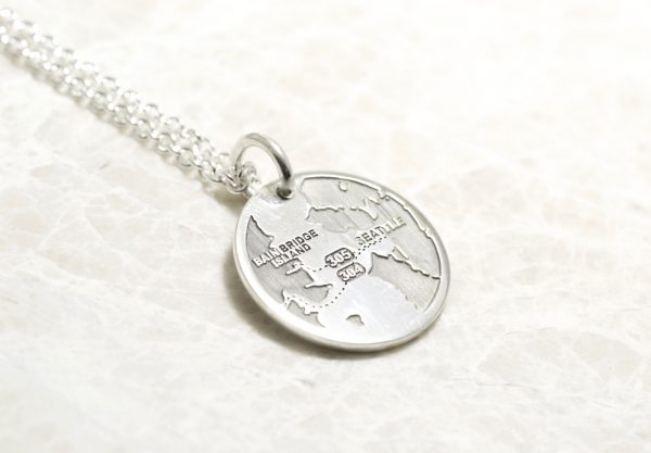 A Personalized Round Necklace With The Map Of Your Special Location